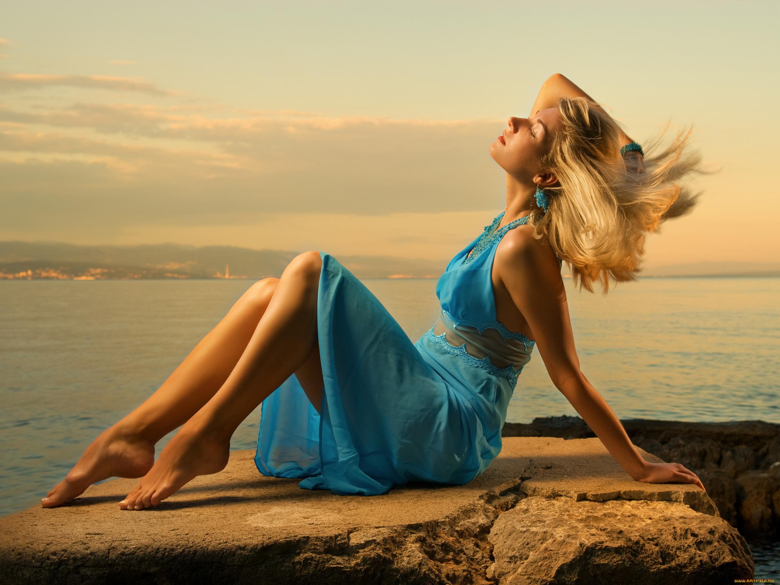 Молодая блонда позирует на берегу моря  116485